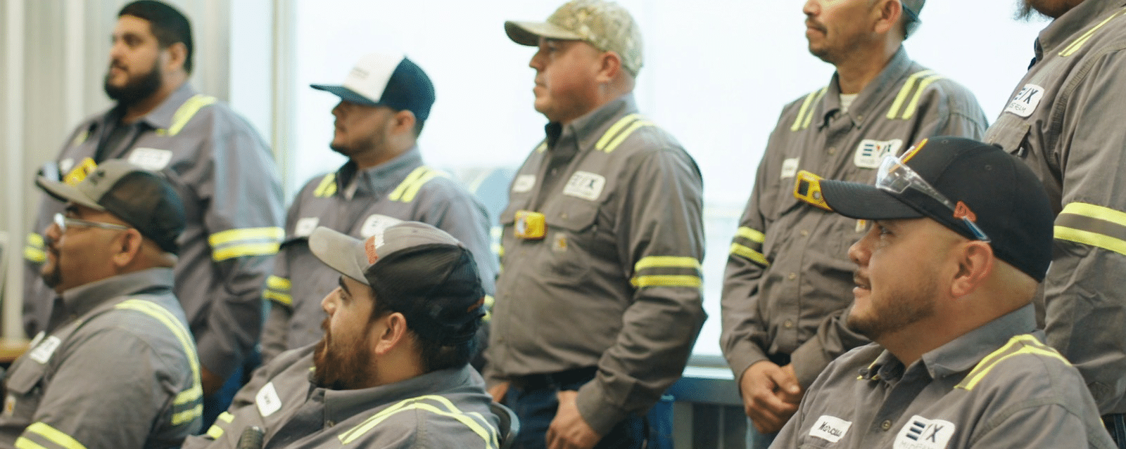 Eight workers listening to a speaker during a company meeting.