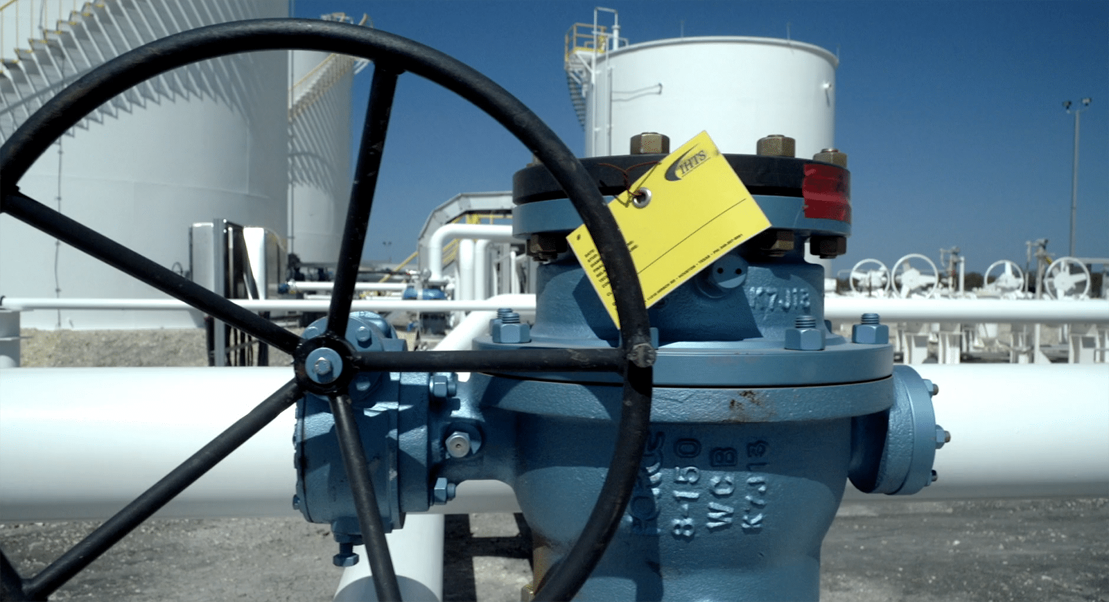 Close-up of a shutoff valve in front of two outdoor water storage tanks and a pipeline.