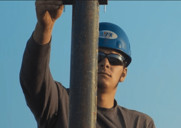 A worker wearing a hardhat inspecting a pipe in the outdoors.