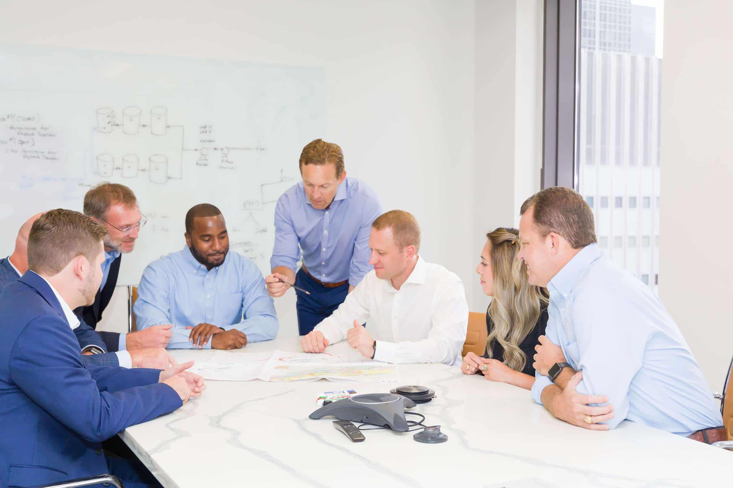 A team of eight employees seated at an office conference table reviewing documents.