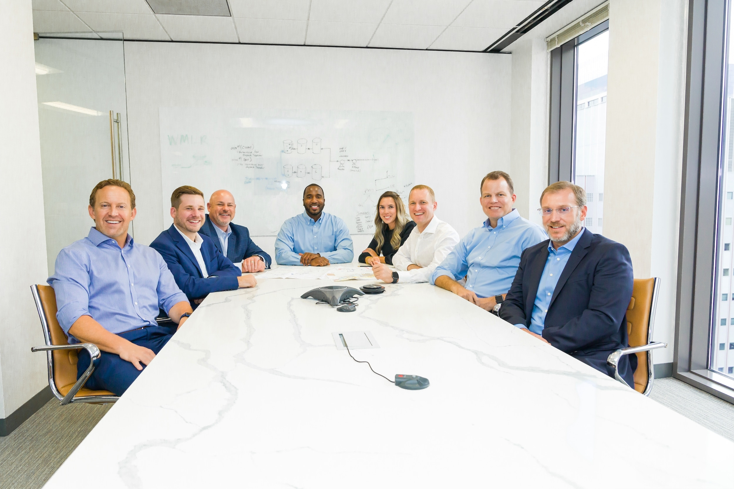 A team of eight employees seated at an office conference table posing for a group photo.