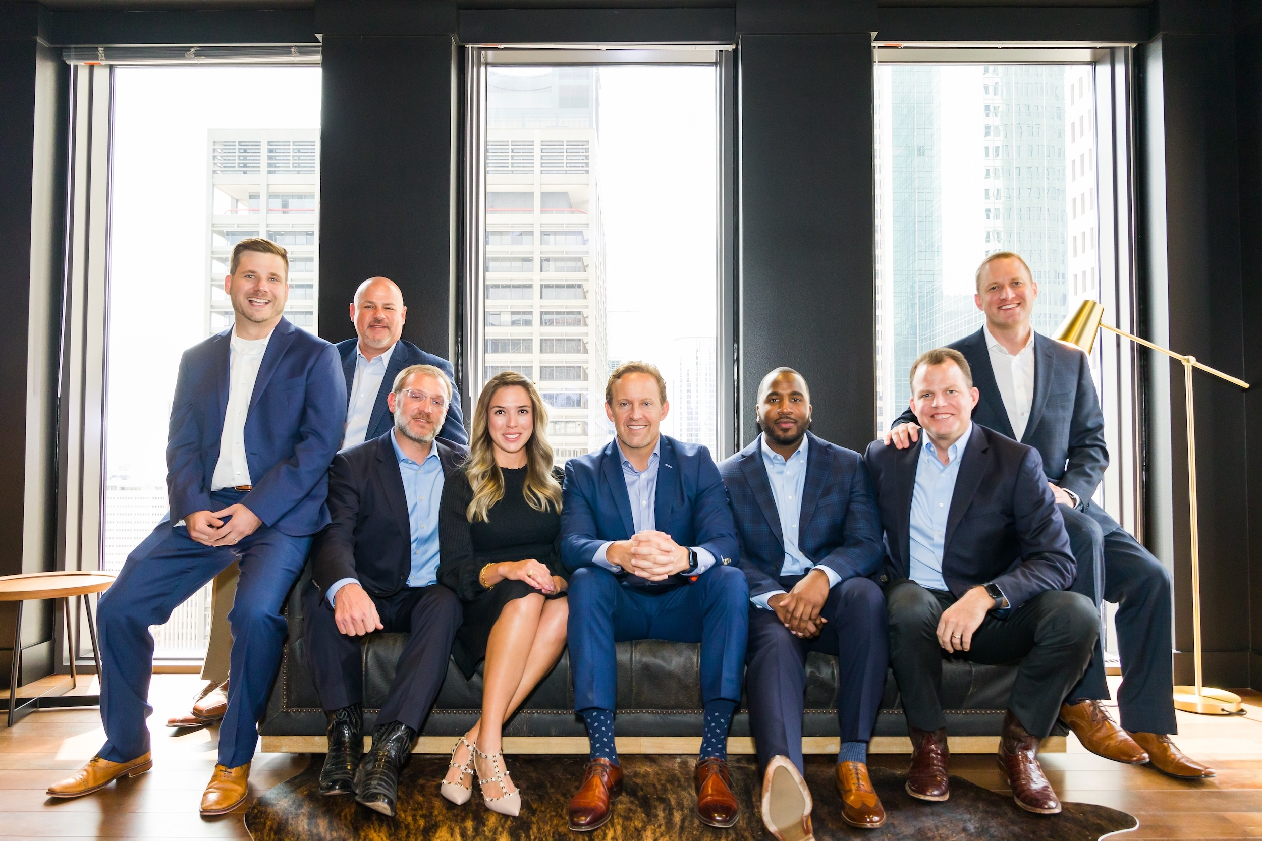The EVX Midstream leadership team seated on a large couch posing for a group photo.