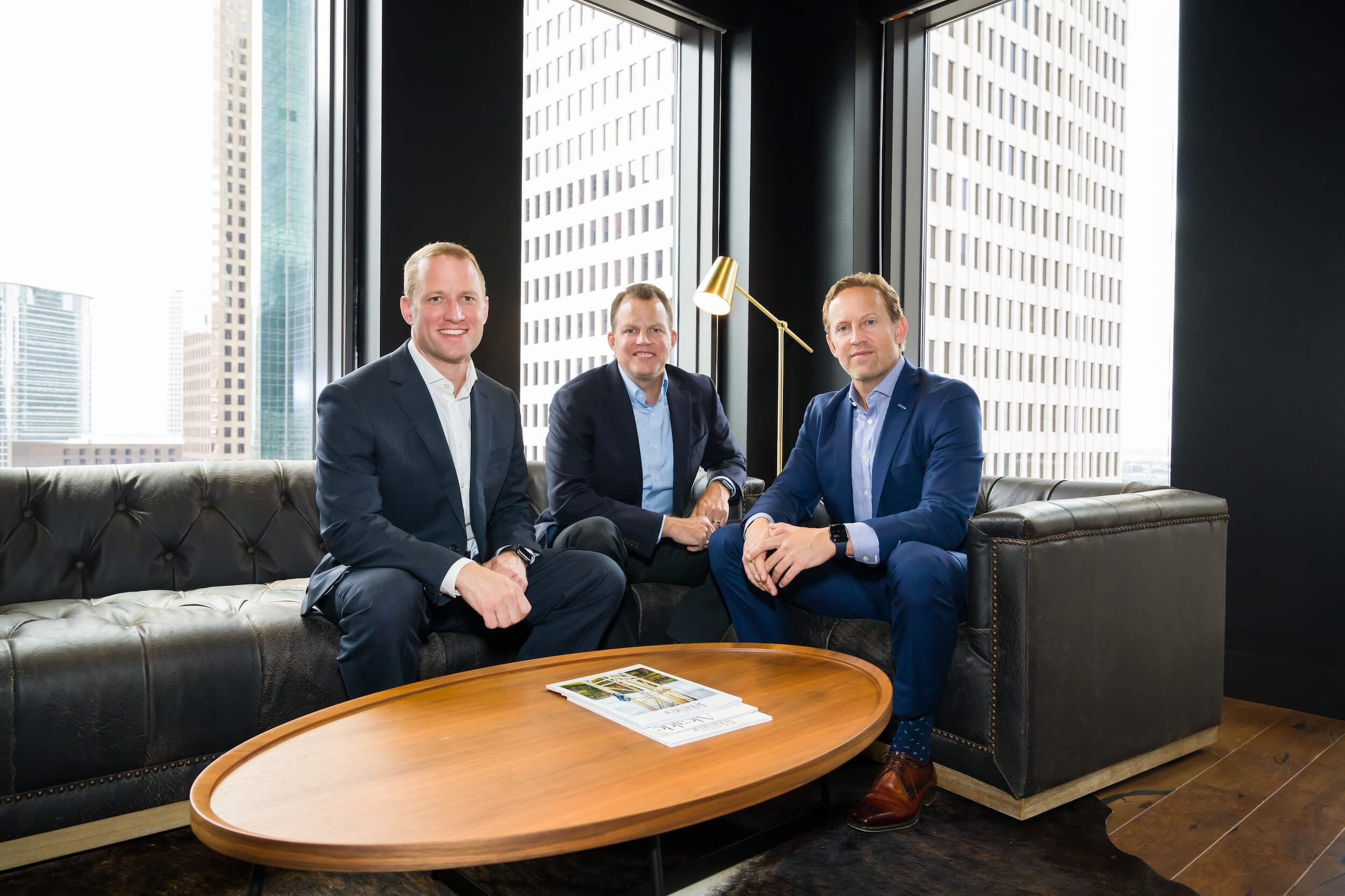 Three co-workers seated at a coffee table posing for a group photo.