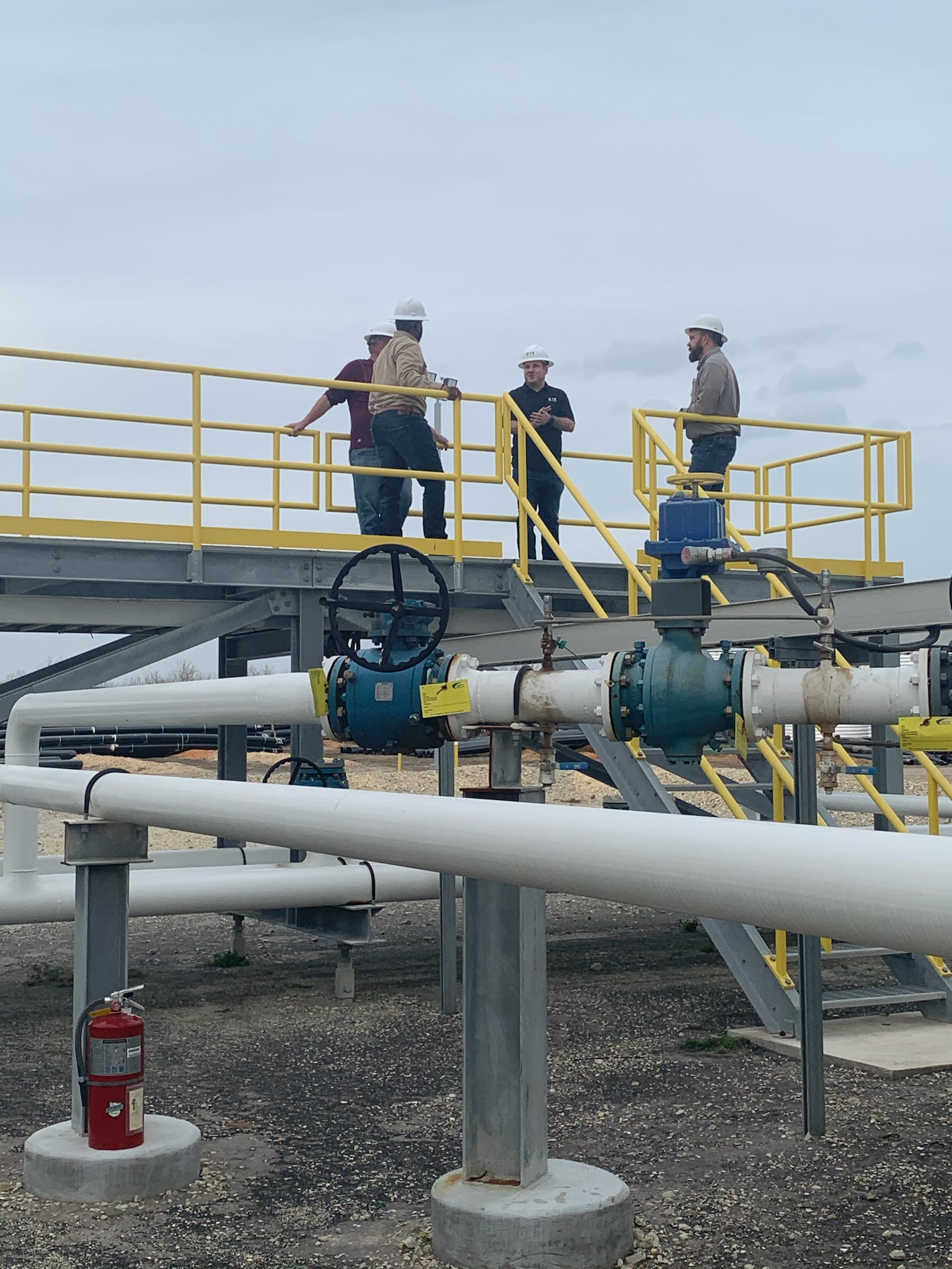 Four co-workers standing on a platform above a series of pipelines.