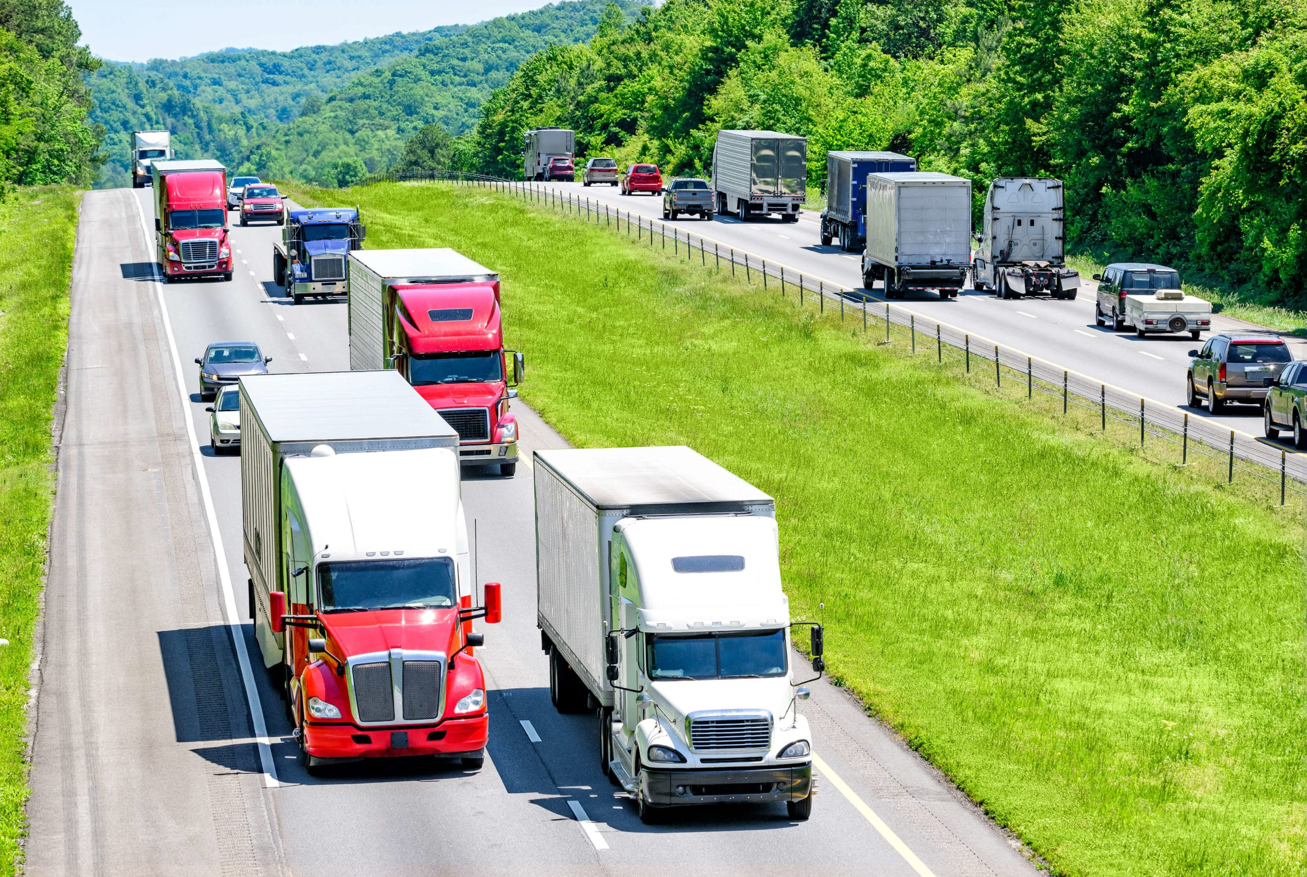 Large trucks traveling up and down a busy freeway in the countryside.